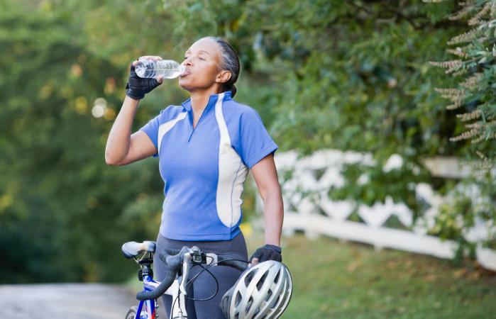Senior female cyclist drinking water