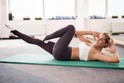 Young female athlete exercising sit-ups in a health club