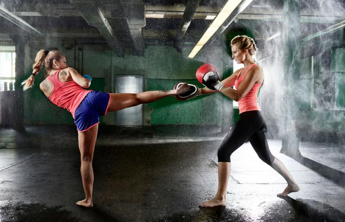 Two women kickbox