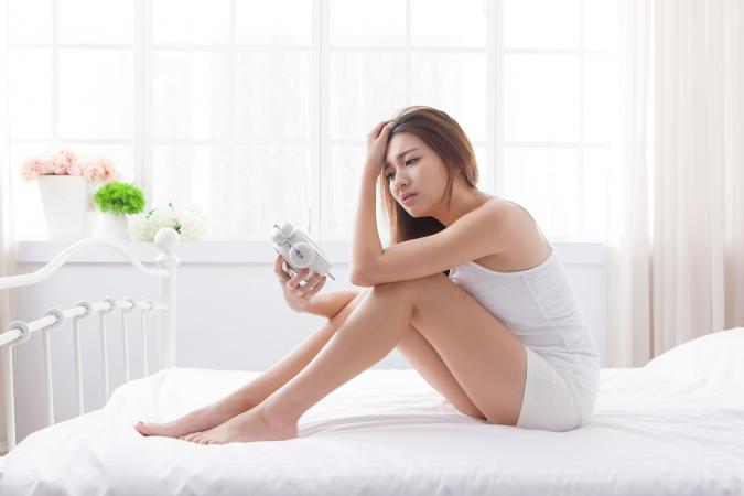 Woman on bed looking at clock