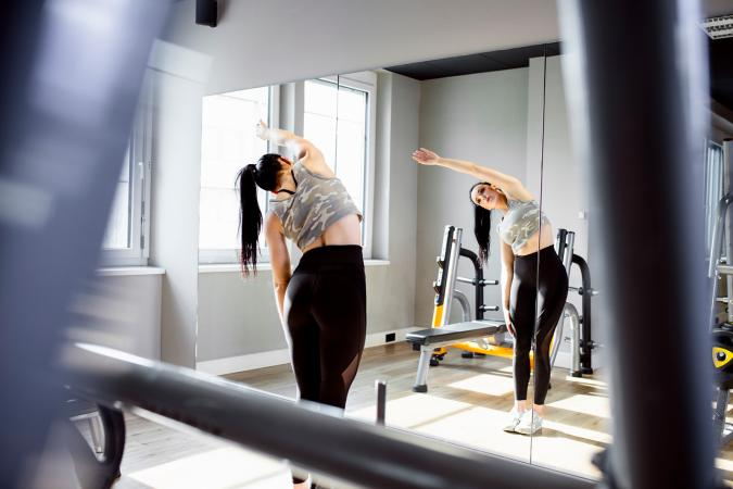 Woman stretching in front of mirror
