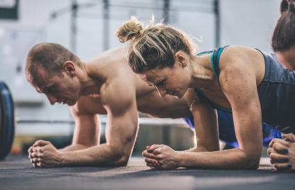 Man and woman doing plank exercises at the gym