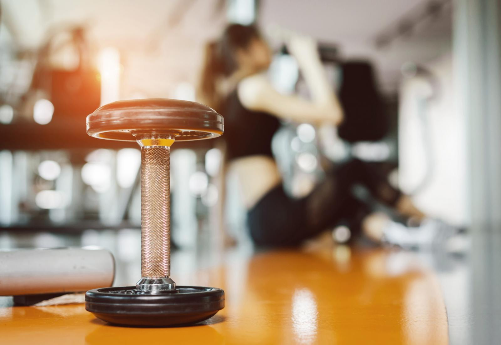Dumbbell With Woman Sitting In Background