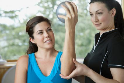 Woman doing elbow exercise with therapist