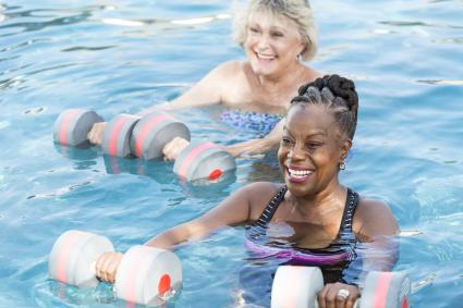 Two women standing in a swimming pool holding dumbbells