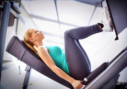Woman exercising on leg press machine