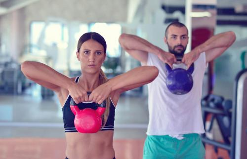 Kettlebells swing exercise man and woman