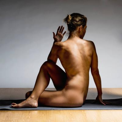 Nude woman practicing pilates