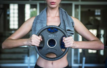 Fitness woman lifting weights in gym