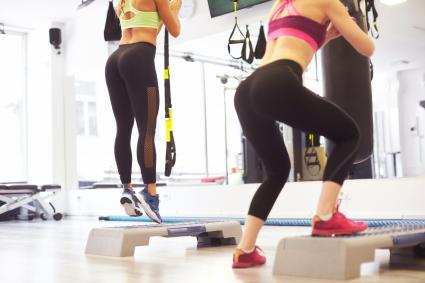 Two women doing lunge stairs in the gym