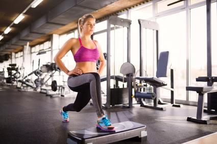 Woman doing lunges on step aerobics equipment at gym