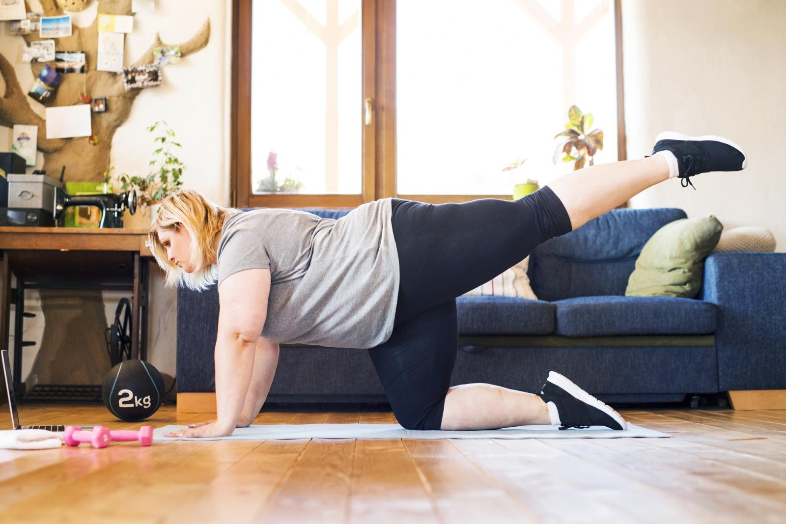 Overweight woman at home working out