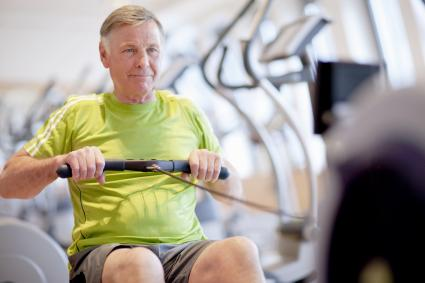 Senior man exercising on rowing machine in gym