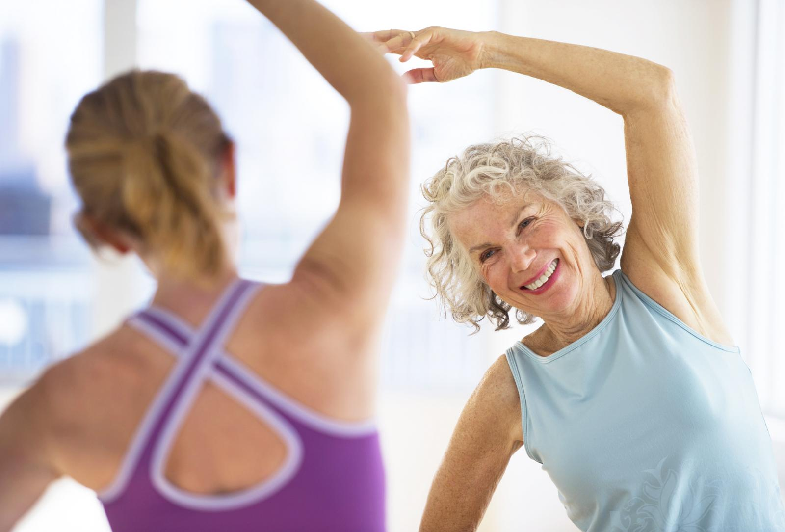 Senior woman with fitness instructor at gym - stock photo