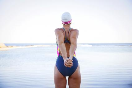 Female open water swimmer stretching arms at ocean