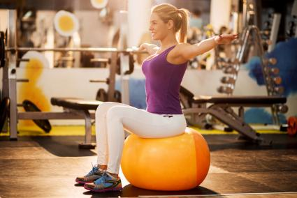 Woman doing hip stretch exercises on a fitness ball at gym