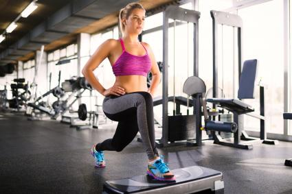 Woman doing standing hip flexor stretches on step aerobics equipment at gym