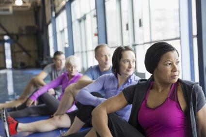 People stretching their hips in exercise class
