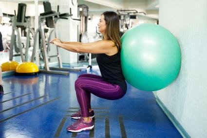 Woman doing squatting with exercise ball