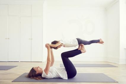 Daughter balancing on mothers legs