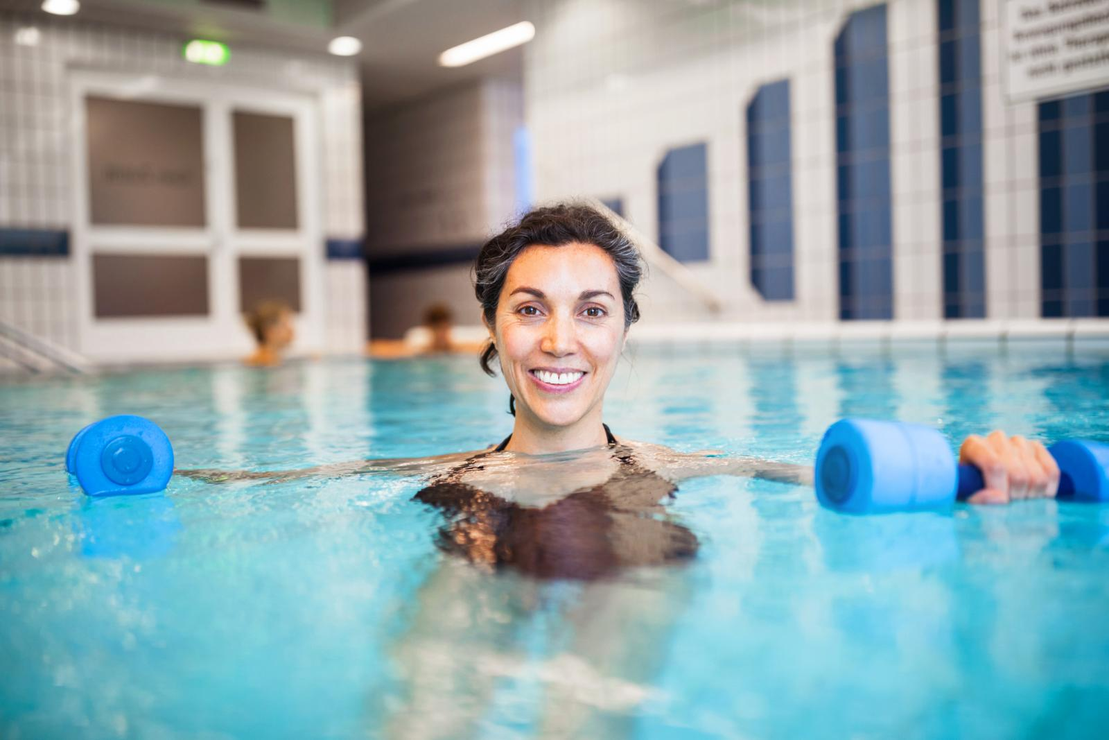 Woman exercising with dumbbells in swimming pool