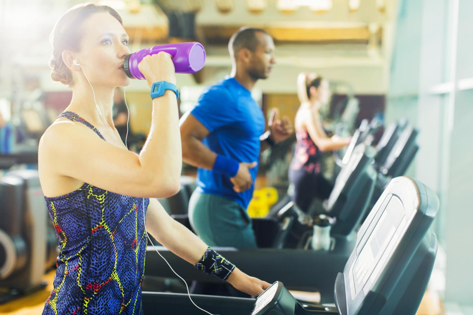 Woman on treadmill drinking water