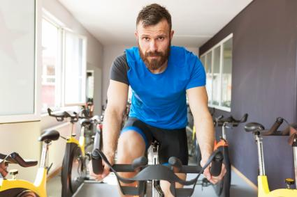 Man using exercising machine in gym