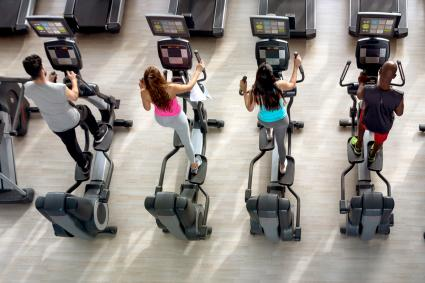 Group of people at the gym on the elliptical machine