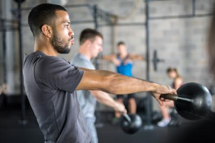 Men exercising with kettlebell in gym