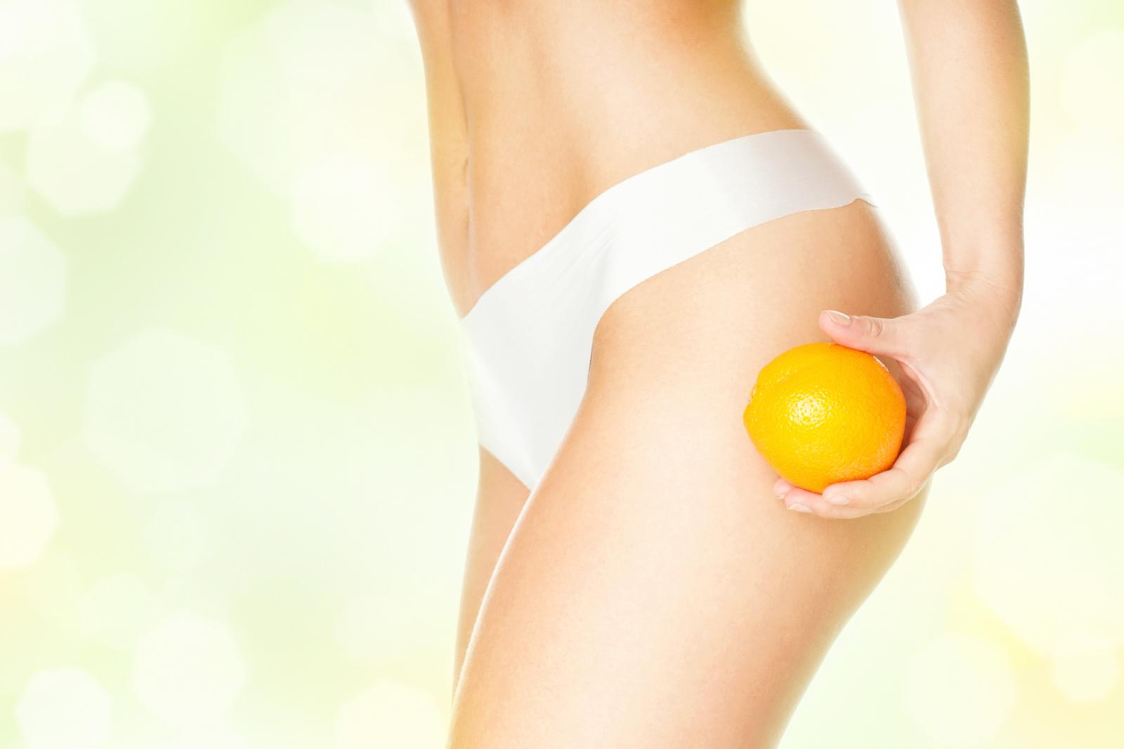 Woman in white underpants holding an orange