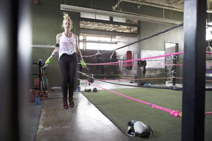 Female boxer jumping rope next to boxing ring
