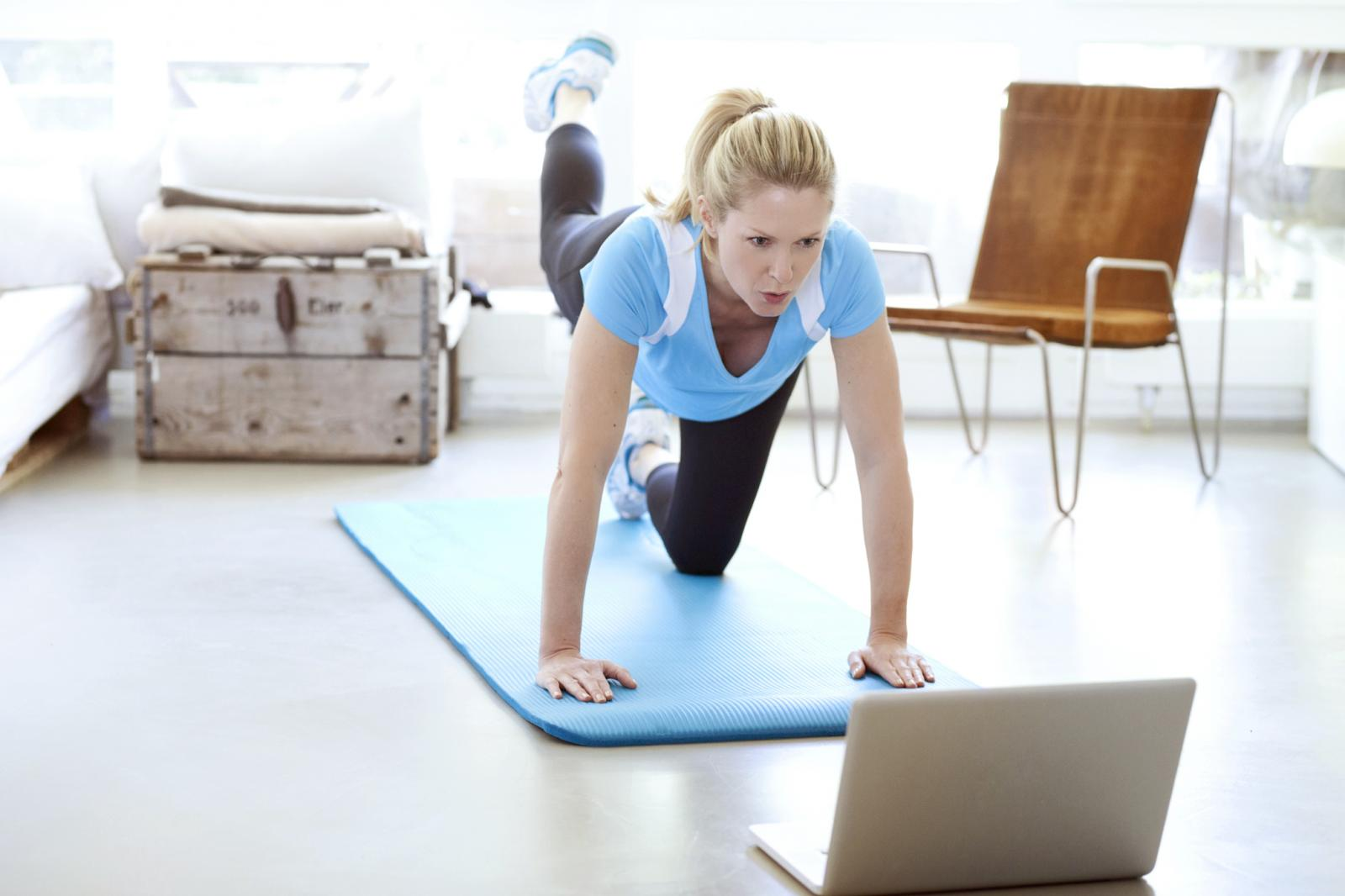 Woman looking at laptop exercising on gym mat in living room