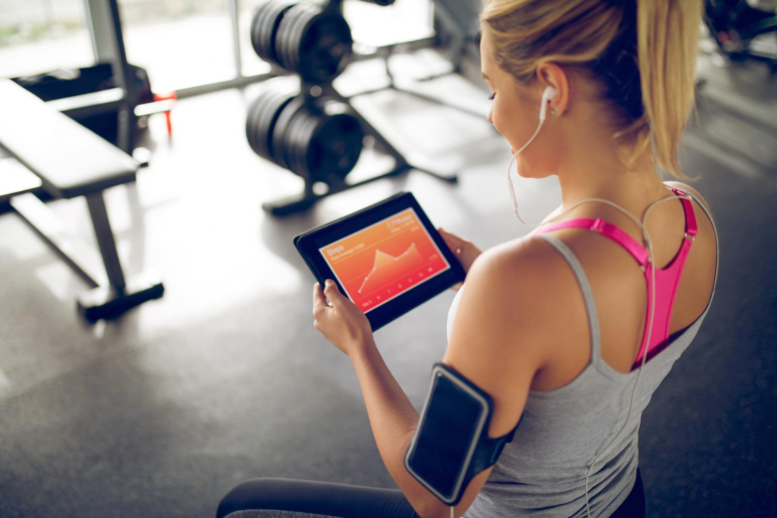 Tracking her progress with fitness app on digital tablet