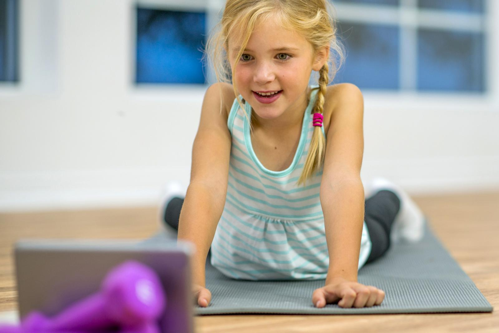 An elementary age girl is doing yoga on an exercise mat