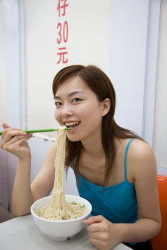 Chinese woman eating noodles