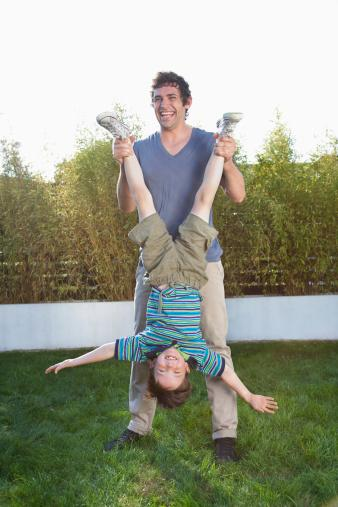 Father holding son upside-down