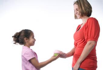 girl handing cupcake to adult