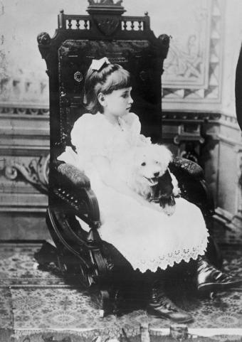 Young Helen Keller holding poodle