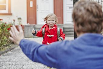 Happy daughter approaching father at house entrance