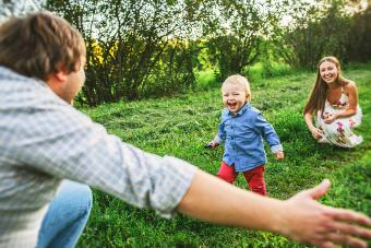 Parents playing with toddler son outdoors