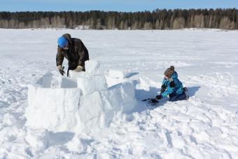 Man and boy building igloo