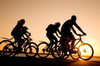 Family riding bicycles at sunset