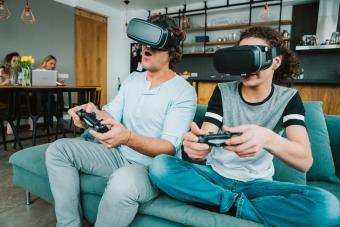 Father and teenage boy playing VR game