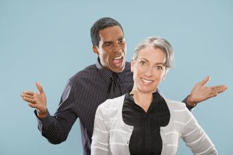 Man yelling at a woman who is smiling