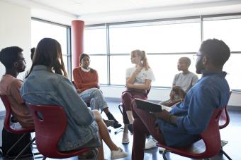 Woman sharing while sitting with mental health instructor in group meeting