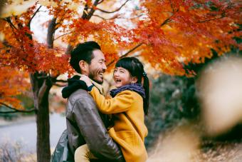 Father holding cheerful little girl under autumn leaves