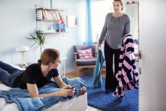 Angry woman holding clothes while looking at son lying on bed