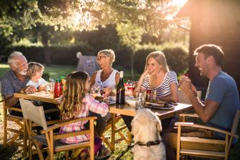 Happy multi-generation family enjoying dinner time at their backyard