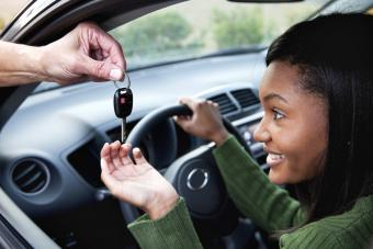 Young woman eagerly takes car key handed to her