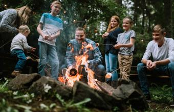 family enjoys relaxing by a fire